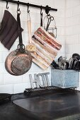 Rustic kitchen utensils hung from rod above kitchen cooker