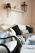 Black and white arrangement of many scatter cushions, fur throw and blanket on comfortable sofa