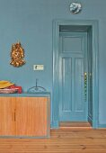 Low sideboard against blue-grey wall and next to door of same colour