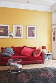Scatter cushions on red sofa below pictures on yellow wall and side table on rug in period apartment