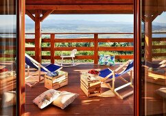 Loungers with wooden crates used as side tables on balcony