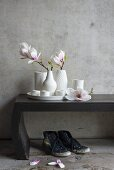Magnolia flowers in white vases on wooden bench against concrete wall
