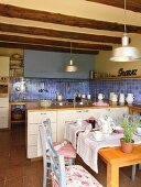 Blue wall tiles, wood-beamed ceiling and runner on set dining table in country-house kitchen