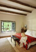 Red tartan blanket on bed, antique bedroom bench and open window