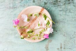 Edible mallow flowers on plate (top view)