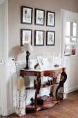 Carved antique console table against white wainscoting in traditional interior