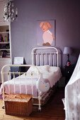 White metal bed below picture of rabbit on purple wall in vintage-style child's bedroom