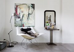 Animal-skin blanket on designer rocking chair below picture of elephant, industrial-style standard lamp and drinks table
