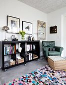 Black bookcase on castors next to green leather armchair in corner and footstool on colourful rug