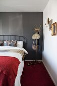 Metal bed and old coat stand against black wall