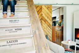 Restaurierte Holztreppe mit Botschaften und Blick auf Kaminfeuer und Küche