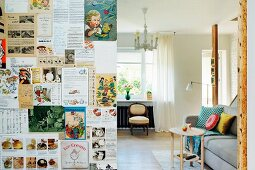 Partition wall papered with magazine clippings and view into living room