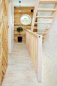 Helle Holztreppe und rustikale Wandverkleidung in renoviertem Altbau mit rundem Fenster