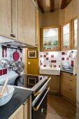 Einbauküche mit Vitrinen-Oberschränken und Porzellanspülbecken