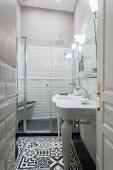 Schmales Bad mit weißem Waschtisch und schwarz-weissem Ornamentfliesenboden