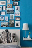 Various framed photos hung in salon style on blue bedroom wall