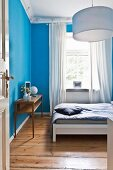 Bedroom with bright blue walls and board floor in restored period apartment