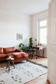 Antique table, vintage office chair, plant stand and leather couch in living area