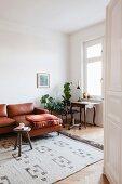 Antiker Tisch mit Vintage Bürostuhl und Blumenständer in Wohnbereich mit Ledercouch