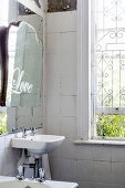 Old mirror in vintage-style bathroom with window grille