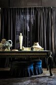 Sculpture on baroque table in front of dark curtain