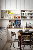 Open-fronted shelves and dining area in white country-house kitchen