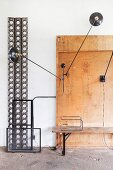 Black wall lamps bolted to rustic wooden board