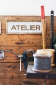 Vice on workbench in front of sign on rustic board wall