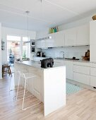 Elephant ornament on island counter in white fitted kitchen