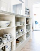 Blue and white crockery in open-fronted shelves below kitchen counter