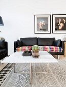 Coffee table with white marble top in front of black leather two-seater sofa with colourful blanket on seat