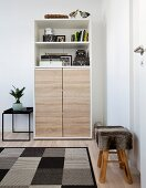 Stool with fur cover and geometric rug in front of cabinet with oak doors below open shelves