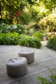 Two pouffes on round wooden deck in summery garden