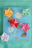 Bunte Origamisterne auf einer bemalten und beklebten Leinwand