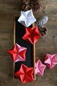 Bunte Origamisterne, eine Tafel und Zapfen auf Holzbrettern