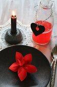 Roter Origamistern auf einem schwarzen Teller, rotes Getränk