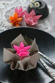 Origami flowers on black plate with raised pattern