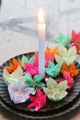 Colourful origami flowers and candle on black plates
