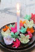 Bunte kleine Origami-Blumen auf schwarzen Tellern mit einer Kerze