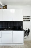 White kitchen with black worksurface and splashback