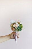 Delicate winter posy of flowers and succulents held in woman's hand