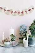 Arrangement of plants and lit white candles below garland on wall