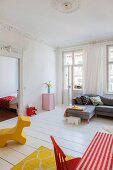 Grey corner sofa, balcony doors and toys in period apartment