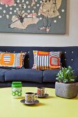 Retro cups on coffee table in front of patterned scatter cushions on sofa