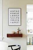 Graphic alphabet artwork above wooden wall-mounted shelf