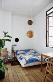 Bed with bedspread on wooden floor in period apartment