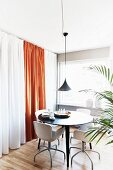 Pendant lamps and curtains in elegant dining area