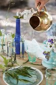 Pouring water from brass jug into glass on table set with summer flowers