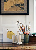 Collection of paint brushes in ceramic pot next to artistic white vases holding dry twigs