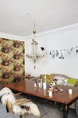 Vintage wooden table and crystal chandelier in front of accent wall with floral wallpaper